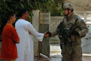 soldier shaking hands with an Iraqi
